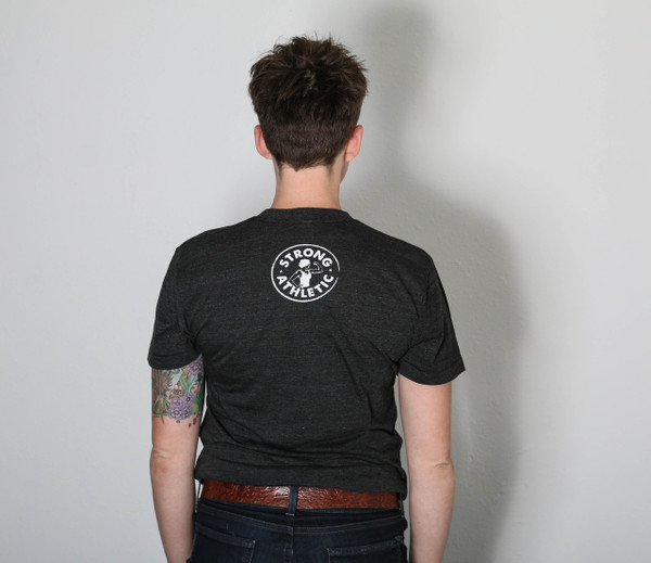 """This is the back of the Strong Athletic Coach t-shirt. We've had a few people call our shirts """"shirts for women"""" when they see that our logo has a woman on it. The way we see is it is that a strong woman should be something that everyone is proud to have on their chest, or in this case on their back, not just people who identify as female."""