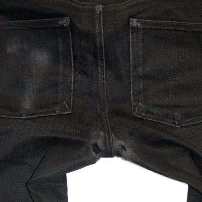 Crotch blowout holes on black Naked and Famous jeans.