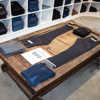 raw denim jeans sale inside store display on buddha bed