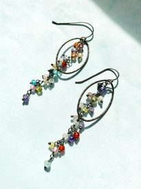 Long dangle earrings designed with silver oval loops.