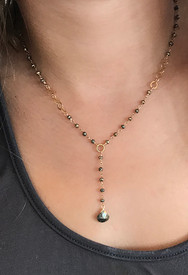 A wire wrapped rosary chain, a golden ring and pyrite stone