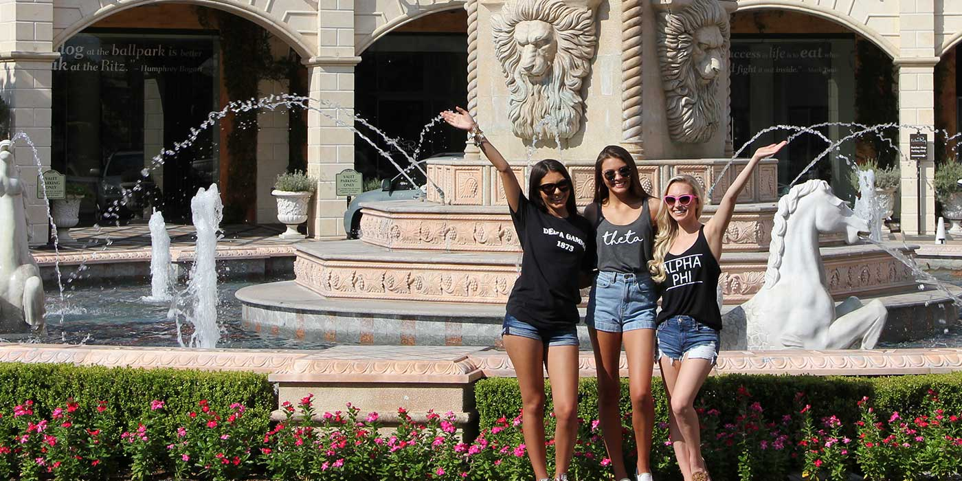 three girls standing in front of fountain