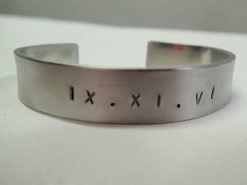 Metal hand stamped silver bracelet with sobriety date in roman numerals.