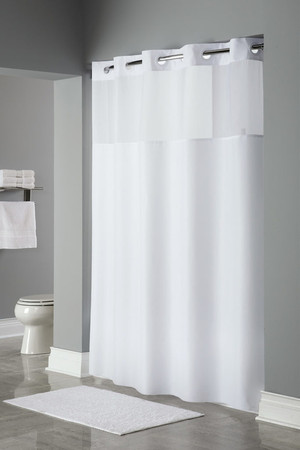 "Available in different styles to complement any decor, the Mystery Hookless® shower curtain is not only handsome - it's also extra durable because it's made for hotels. The Mystery Hookless® shower curtain installs in seconds and operates smoothly without tugging or snagging. The Mystery Hookless® shower curtain curtain ""stacks"" beautifully for a neat appearance when pushed to the side. The Mystery Hookless® shower curtain works with any shower rod, but combine it with The Arc ™ for an elegant upgrade. Constructed of our subtle plainweave 100% polyester fabric, the Mystery Hookless® shower curtain provides the added feature of a translucent voile window to allow light into the shower.  100% polyester with sheer window Water repellent 71 x 74 or 71 x 77 inches Built-in magnets Available in white and beige Call 855-468-3528 or click here to email us about large quantity purchases."