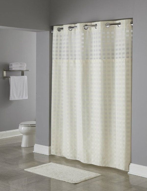 "Available in different styles to complement any decor, the Shimmy Square Hookless® shower curtain is not only handsome - it's also extra durable because it's made for hotels. The Shimmy Square Hookless® shower curtain installs in seconds and operates smoothly without tugging or snagging. The Shimmy Square Hookless® shower curtain ""stacks"" beautifully for a neat appearance when pushed to the side. The Shimmy Square Hookless® Shower Curtain with ""It's A Snap""™ liner works with any shower rod, but combine it with The Arc ™ curved shower rod for an elegant upgrade. The Shimmy Square Hookless® shower curtain is a one of a kind sheer and strong check weave design Hookless® shower blind built of 100% polyester. Check weave finished pattern stretches out through the sheer voile window for included style.      100% Polyester fabric with coordinating sheer fabric window     Two piece set including replaceable Snap-in Liner     Water repellent snap-in liner resists soap scum and minimizes mold and mildew     Chrome raised Flex-On rings allow 10 second installation without removing the shower rod     71 x 77     71x77     Available in white and beige   Call 855-468-3528 or click here to email us about large quantity purchases."