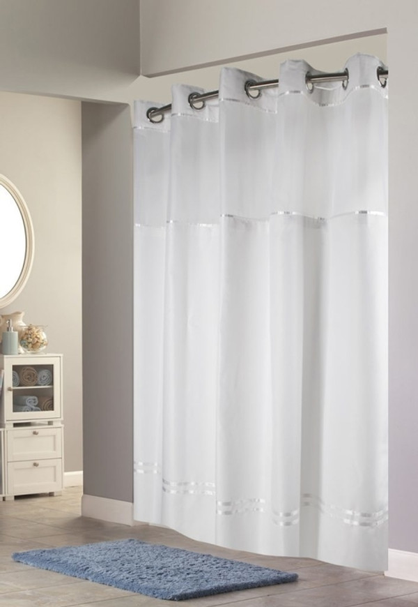 """Available in different styles to complement any decor, the Escape Hookless® shower curtain is not only handsome - it's also extra durable because it's made for hotels. It installs in seconds and operates smoothly without tugging or snagging.  The Escape Hookless® shower curtain """"stacks"""" beautifully for a neat appearance when pushed to the side. The Escape Hookless® shower curtain with """"It's A Snap""""™ liner works with any shower rod, but combine it with The Arc ™ for an elegant upgrade. Form meets function with the Escape Hookless® shower curtain program. Satin accent stripes enhance the low maintenance of 100% polyester plainweave fabric. The Escape Hookless® shower curtain collection has been a pillar and true top seller among our Hookless® shower curtains. The clean luxury of the Escape Hookless® shower curtain makes it an easy setup for many bathroom decors. We offer the ability to customize the key visual details to make the escape truly unique to your home/ business property.   Water repellent Chrome plated rings Heavy duty snaps with flap to prevent leakage Washable and dry-able white polyester cloth liner Treated to resist soap scum and minimize mold and mildew Available in White or Ivory, each with decorative, polyester silk tone-on-tone ribbons Also available in White or Sand, each with decorative polyester silk contrasting Brown or Black ribbons Call 855-468-3528 or click here to email us about large quantity purchases."""