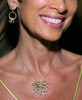 Close up of Superstar pendant and Circle Fireworks Earrings on designer Jane A Gordon, at Jane Gordon Jewelry
