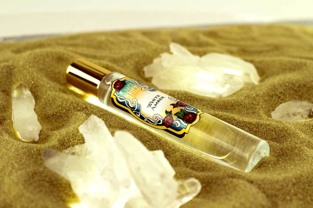 White Amber rollerball perfume laying on a sandy beach  and surrounded by quartz crystal points. This gorgeous fragrance is indescribable like the scent of your warm skin in an ocean breeze. It is one of the Flower Thief perfume line by Elixery.
