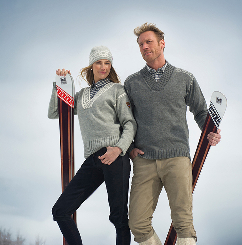Couple ready to ski while wearing their Dale of Norway Alpina sweaters--ladies, in Light Charcoal/Cream 92531-E, and mens, in Smoke/Light Charcoal, 92541-E
