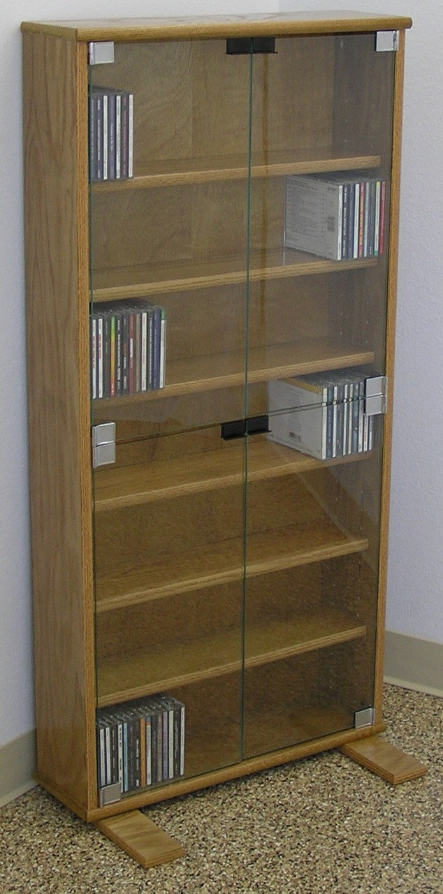Dvd storage cabinet 48h shown in light brown oak with clear glass doors