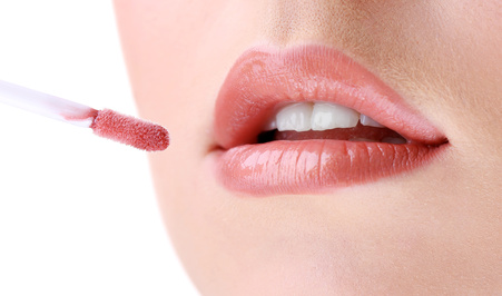 woman-applying-natural-lip-gloss-to-mouth-closeup.jpg