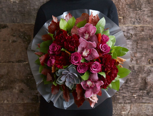 Cozy up by the bonfire with this stunning collection of deep pinks and reds. Textural carnations create gatherings around deep cerise roses whilst a scattering of pink orchids creates an ultimately luxurious feel. The flowers are hand-tied together with a mixture of green and deep red foliages, and the whole design is finished with gorgeous purple Succulent plant that you can re purpose and plant once the rest of the arrangement has faded.  Like all of our bouquets, 'Bonfire Berry' is made by one of our talented florists using the highest quality flowers, beautifully gift wrapped and finished with a hand written card.