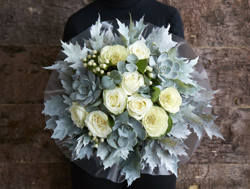 'Frozen Dewdrops' is inspired by late Autumn mornings, the clouds of your breath as you step outside and the crunch of first steps onto frosted grass. Fresh white roses, brassicas and hypercium berries bunched together with lashings of silvery blue eucalyptus and painted white oak - finished with a trio of gorgeous Succulent plants that you can re purpose and plant once the rest of the arrangement has faded.  Like all of our bouquets, 'Frozen Dewdrops' is made by one of our talented florists using the highest quality flowers, beautifully gift wrapped and finished with a hand written card.