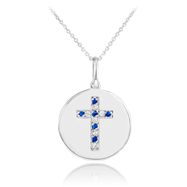 Cross disc pendant necklace with diamonds and sapphire in 14k white gold.