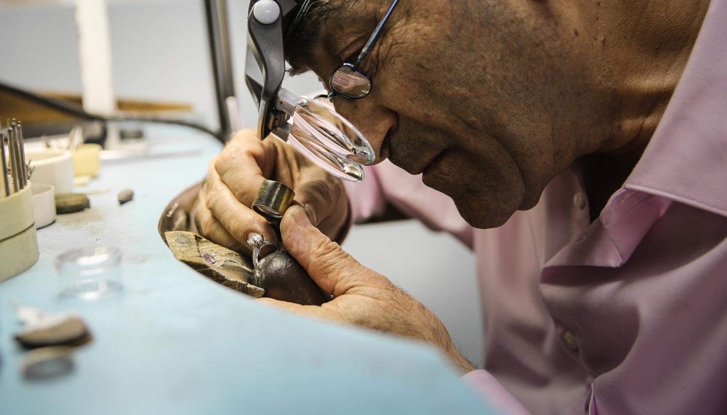 a jewelry craftsman examining a diamond ring