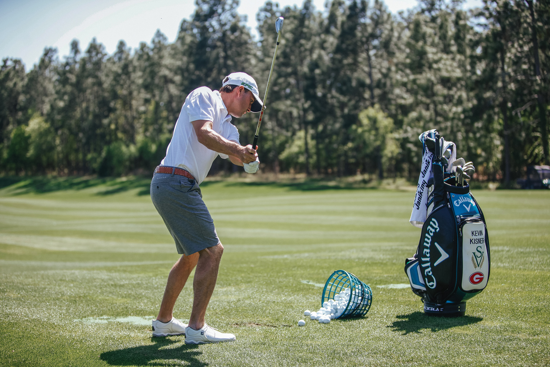 Golfer standing by bag of clubs and basket of balls