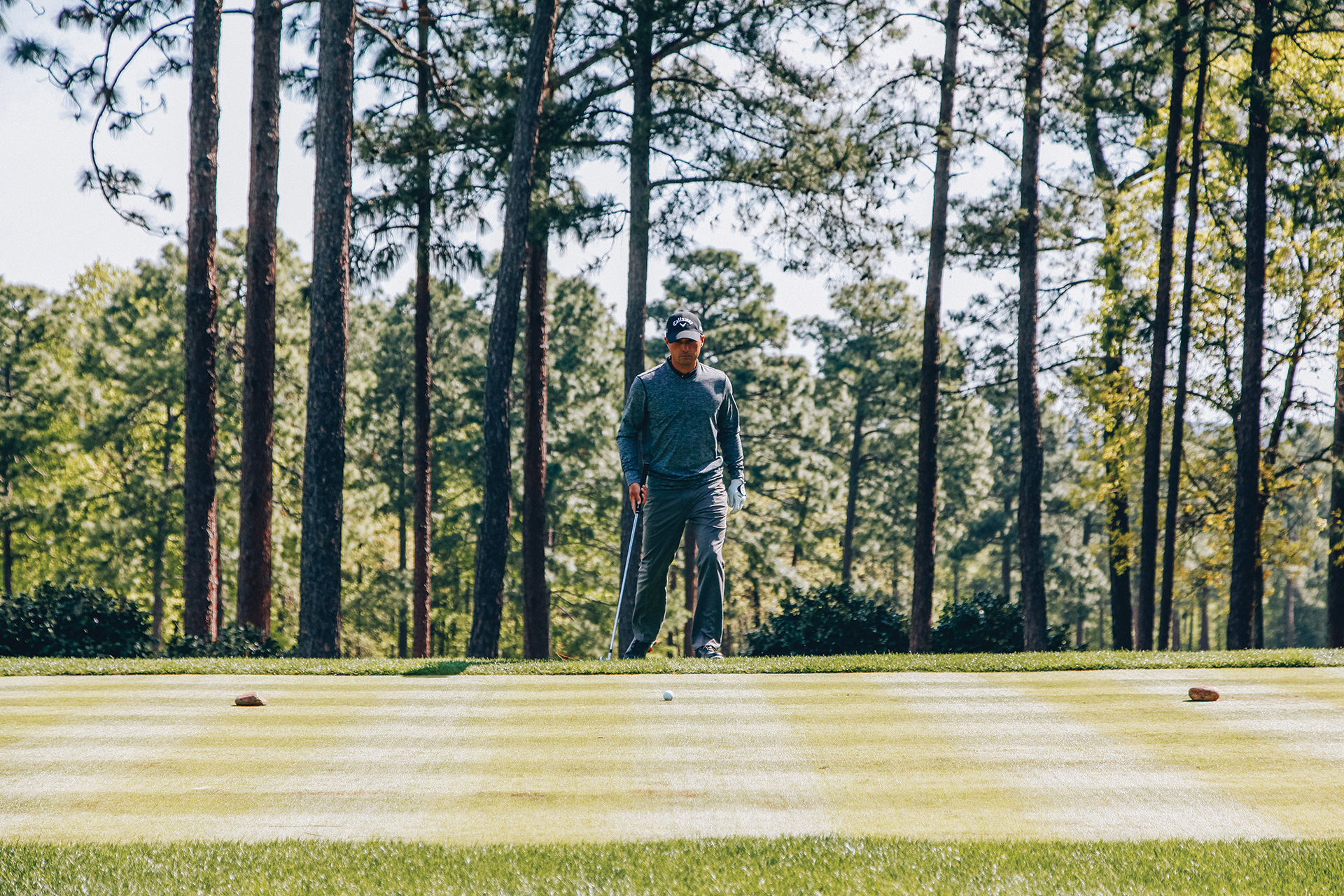 Golfer approaching ball on putting green
