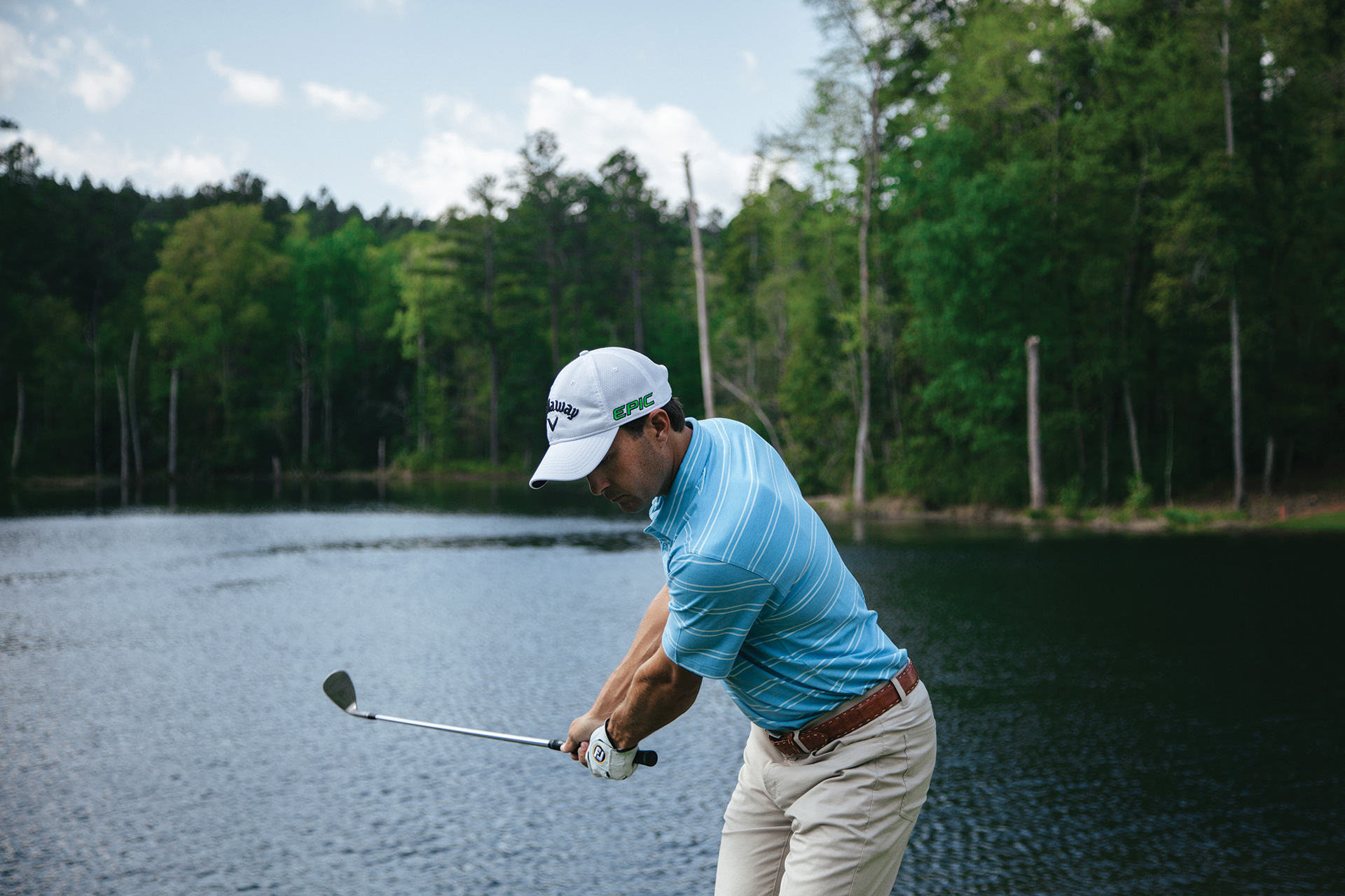 Golfer standing in front of a lake