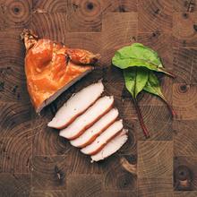 Hot smoked chicken sliced on chopping board