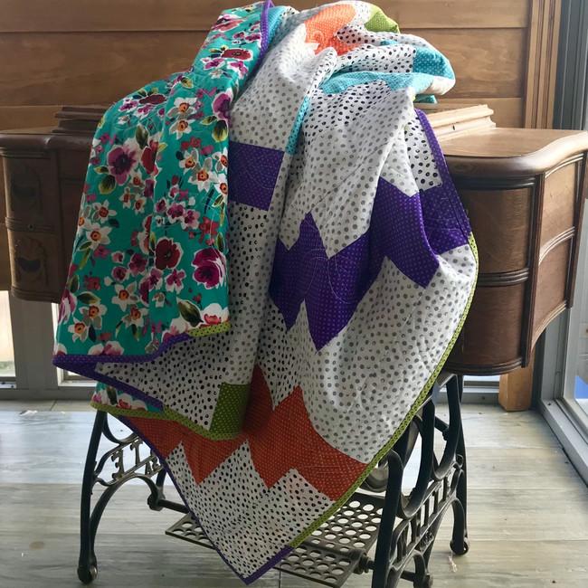 Polka dot fabrics zig zag across the quilt to form a fun pattern. Cotton fabrics and cotton batting. Machine sewn.
