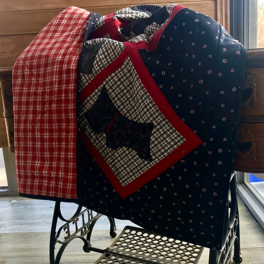8 little appliquéd dogs dance across this quilt with red ribbon collars. Cotton fabrics and cotton batting. Machine sewn.