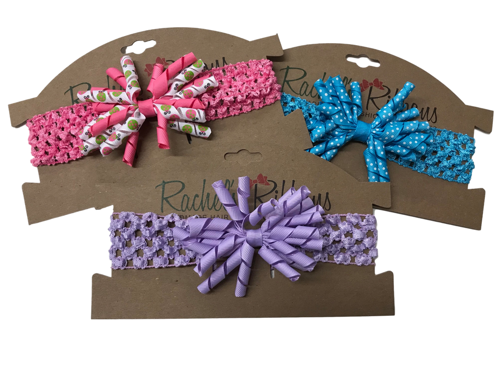 "A stretch crochet band topped with a fun Twiddle Bow is sure to look precious on your little girl. Overall width is approximately 6"", comfortably stretches to approximately 8"".  Flower and headband match (or complimentary to patterns in ribbon), unless otherwise requested.  Perfect for newborns through toddlers."