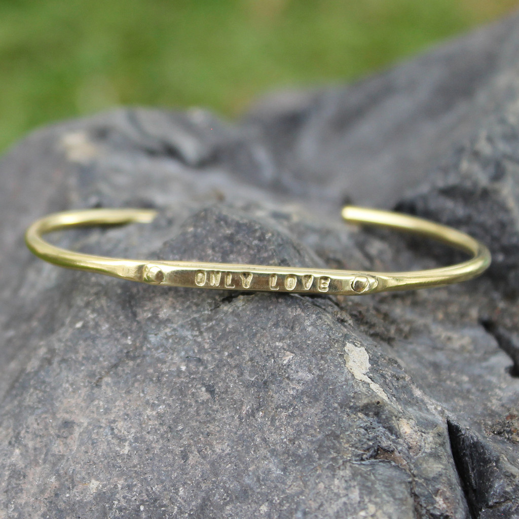 "Brass adjustable bracelet features ""only love"" message"