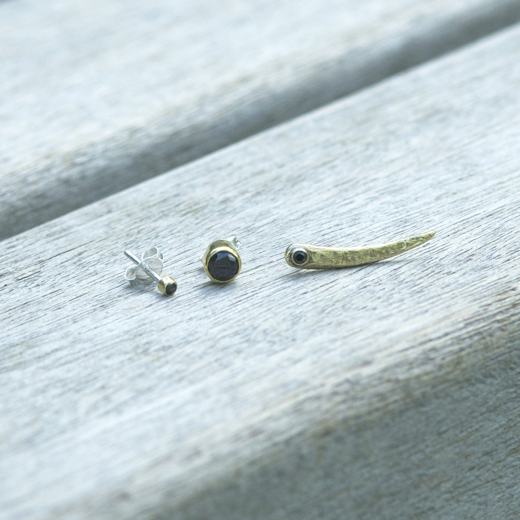 set of three (ear pin and two studs to mismatch) in brass with black stone