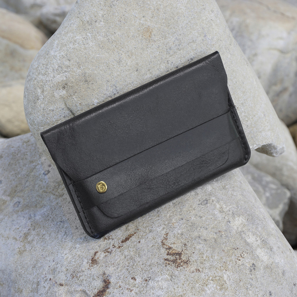black leather card case with 'take more detours' brass plate