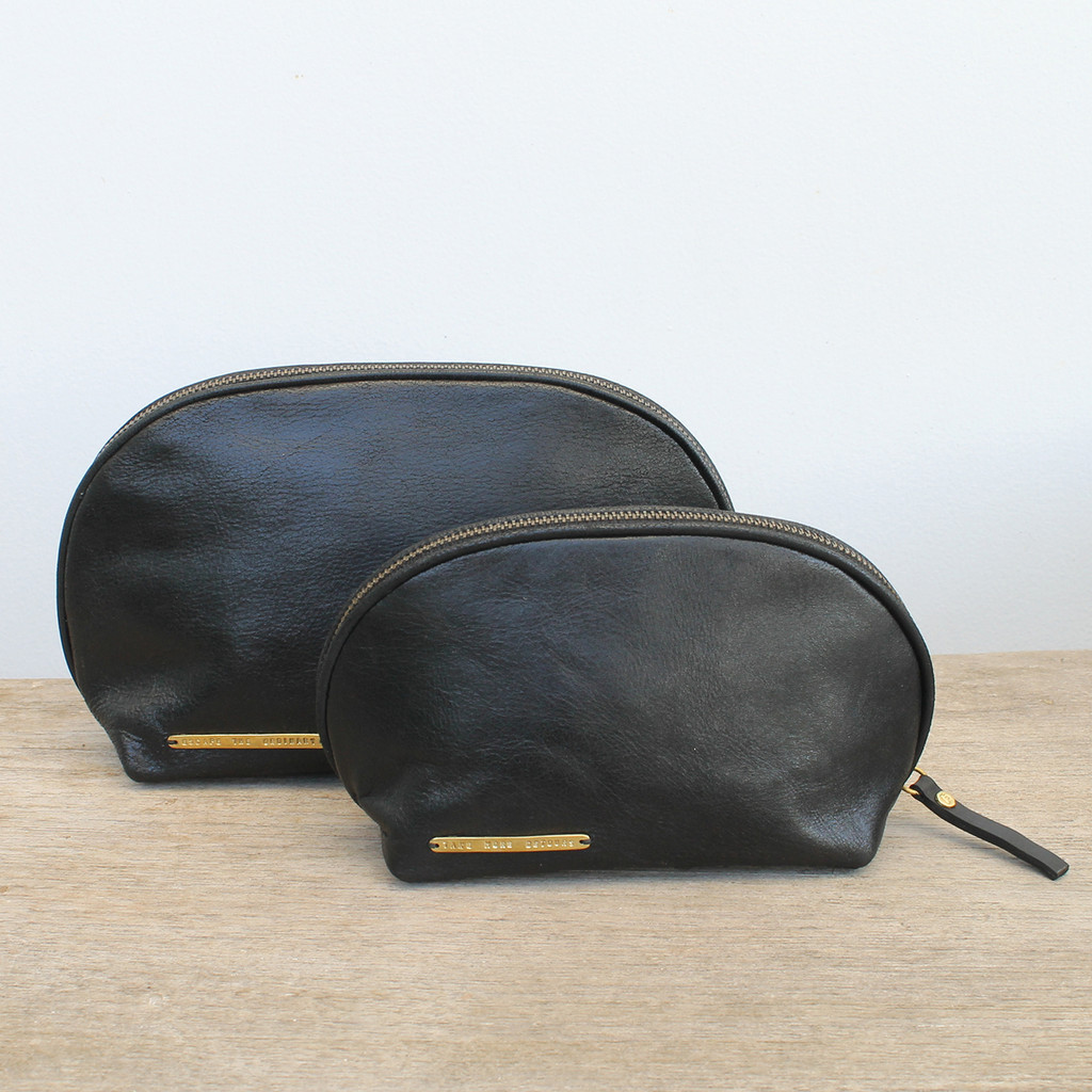 set of two black pouches with 'escape the ordinary' and 'take more detours' brass plates