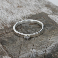 Polished sterling silver ring with raw diamond solitaire setting