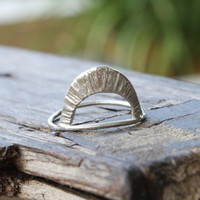 A tall arc ring with radial texture can be worn in either direction in sterling silver.