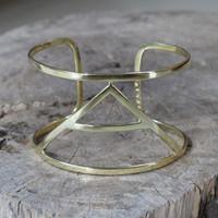 brass statement cuff featuring Explore glyph symbol