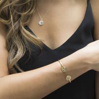 adjustable brass bracelet featuring Protect glyph symbol