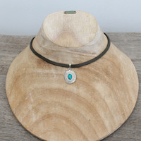 Grey leather with silver plated pendant featuring turquoise stone