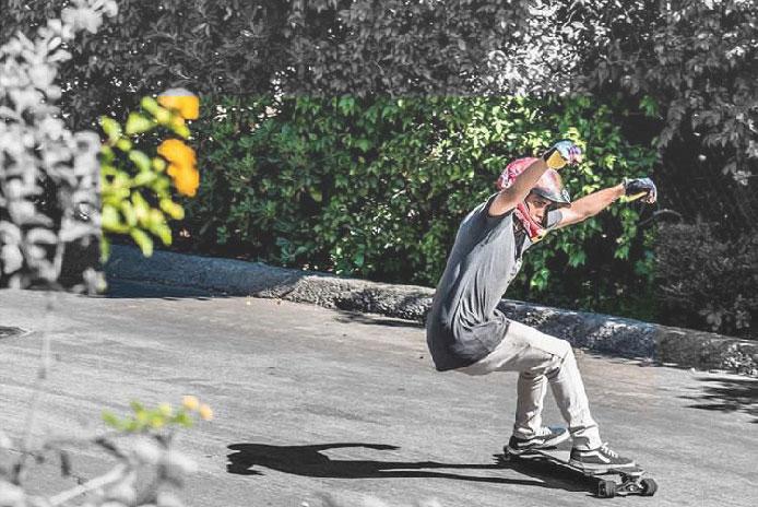 Girl holding a skateboard sitting on a bridge