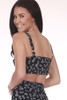 Back shows very cropped hemline black top with small white flower pattern, adjustable thick straps.