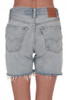 Back  shows mid thigh shredded light denim shorts with pockets.