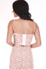 Back shows white and cherry patterned  jumper suit with adjustable spaghetti straps, black slit, and corset hooks.