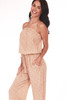 side body shows billowing strapless top with elastic waistband and waist tie, side pockets and jumpsuit is in a blush and white polka dot pattern.
