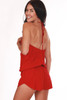 Back shows red drop waist shorts romper with slight slit in side  of shorts and spaghetti strap halter top.