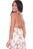 Front shows long white halter dress with allover floral plant design a top ruffle, adjustable halter top. Ties at the neck.
