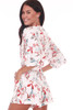 Back shows white shorts romper with allover floral plant pattern, kimono-like sleeves, a wrap front and detachable waist tie.