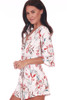 Side shows white shorts romper with allover floral plant pattern, kimono-like sleeves, a wrap front and detachable waist tie.