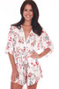 Front shows white shorts romper with allover floral plant pattern, kimono-like sleeves, a wrap front and detachable waist tie.