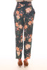 Back shows pink abstract floral print pants with super high rise with belted top, front zipper closure and tapered bottom leg. Shown worn with orange heels.