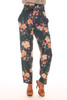 Front shows pink abstract floral print pants with super high rise with belted top, front zipper closure and tapered bottom leg. Shown worn with orange heel.