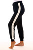 Side shows black jogger pants with white stripes down both sides, elastic band & drawstring top at waist and cuffed ankle bottoms.