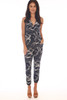 Front shows black and white slash marks design ankle length jumpsuit with a surplice front neckline with snap closure, elastic waistband with tie, rushed bottom hemline. Shown worn with orange open toe heels.