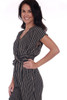 side shows black striped short sleeve jumpsuit featuring a twist front with deep v-neck line, elastic band at waist and tapered skinny legs.